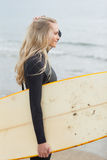 Belle femme dans le vêtement isothermique tenant la planche de surf à la plage Photographie stock