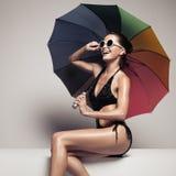 Belle femme dans les vêtements de bain et lunettes de soleil tenant le parapluie Photo libre de droits