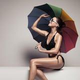 Belle femme dans les vêtements de bain et lunettes de soleil tenant le parapluie Photographie stock