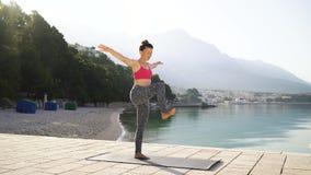 Belle femme dans les vêtements de sport faisant des exercices de yoga au bord de la mer pendant le matin clips vidéos