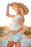 Belle femme dans un chapeau de paille au coucher du soleil photographie stock