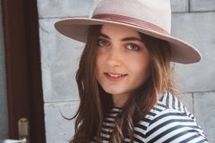 Belle femme dans un chapeau et une chemise ray?e regardant la cam?ra Portrait en gros plan photo stock