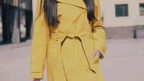 Belle femme dans un chapeau jaune d'imperméable et des promenades en verre en bas de la rue avec le bagage et le sourire banque de vidéos