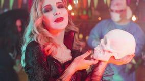 Belle femme dans un costume de Halloween de vampire avec un crâne dans des ses mains banque de vidéos