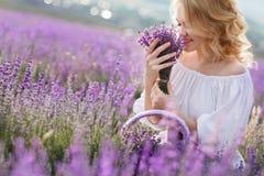 Belle femme dans un domaine de lavande de floraison Photographie stock libre de droits