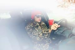 Belle femme dans un manteau de fourrure et un chapeau rouge avec du café à aller driv Image libre de droits