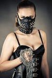 Belle femme dans un masque avec une chaîne photographie stock