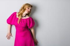 Belle femme dans une robe rose près d'un mur Image stock