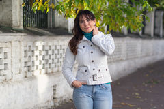 Belle femme dans une veste blanche et des feuilles d'automne photographie stock