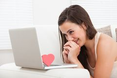 Belle femme datant en ligne sur l'ordinateur portable Image stock