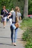 Belle femme de brune au téléphone tout en tenant son bébé dans des ses bras dans la cuisine images libres de droits