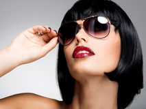 Belle femme de brune avec la coiffure de tir avec les lunettes de soleil rouges Photographie stock