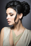 Belle femme de brune avec la peau parfaite, le maquillage d'or et les bijoux faits main Visage de beauté Images stock
