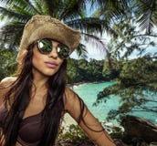 Belle femme de brune avec le chapeau de paille et les lunettes de soleil dans la forêt tropicale Photo libre de droits