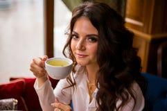 Belle femme de brune buvant le thé vert en café de ville et les regards à la caméra images libres de droits