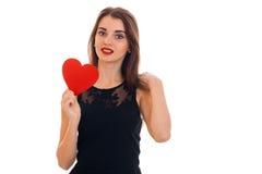 Belle femme de brune dans l'amour posant avec le coeur rouge dans des ses mains d'isolement sur le fond blanc Photographie stock libre de droits