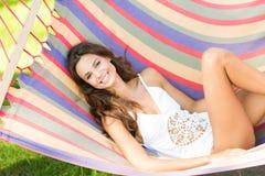 Belle femme de brune dans un maillot de bain blanc dans un hamac photographie stock