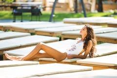 Belle femme de brune dans un maillot de bain blanc près de la piscine Une femme expose au soleil sur une chaise longue blanche photo libre de droits