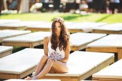 Belle femme de brune dans un maillot de bain blanc près de la piscine Une femme expose au soleil sur une chaise longue blanche images libres de droits