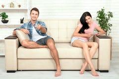 Belle femme de brune de Dissapointed dans la querelle avec son ami Homme indifférent regardant la TV Photographie stock libre de droits
