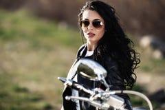 Belle femme de brune de moto avec une moto classique c image stock