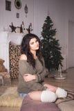 Belle femme de brune en bref et chandail en décor de nouvelle année Photographie stock libre de droits
