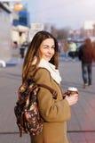 Belle femme de brune jugeant un sac et une tasse de thé ou de café chaud, se tenant dans la rue Images libres de droits