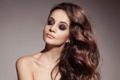 Belle femme de brune. Longs cheveux bouclés. photographie stock