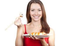 Belle femme de brune mangeant des sushi Images libres de droits
