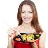 Belle femme de brune mangeant des sushi Image libre de droits