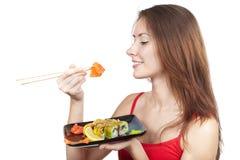 Belle femme de brune mangeant des sushi Photographie stock