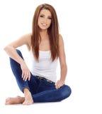 Femme s'asseyant sur le plancher. Pousse de studio. Image libre de droits