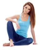 Femme s'asseyant sur le plancher. Pousse de studio. Images stock