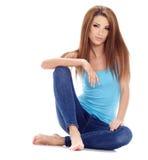 Femme s'asseyant sur le plancher. Pousse de studio. Photo libre de droits