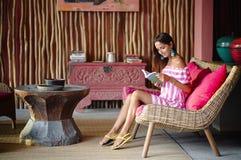 Belle femme de brune s'asseyant sur un divan rose et lisant un livre et un sourire Intérieur dans le style ethnique photos stock