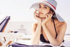 Belle femme de brune sur la plage dans la seule détente de piscine dedans Photographie stock