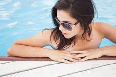 Belle femme de brune sur la plage dans la seule détente de piscine dedans Photo stock