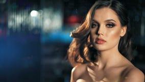 Belle femme de charme dans la robe à la mode posant au-dessus du fond de boker de lumières bleues et rouges clips vidéos