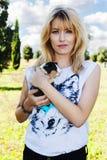 Belle femme de cheveux blonds tenant le lapin mignon d'animal familier Image libre de droits