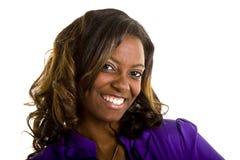 Belle femme de couleur dans le sourire grand de chemisier pourpré Image stock