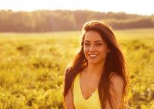 Belle femme de détente de sourire naturelle toothy semblant heureuse avec de longs cheveux étonnants sur le fond lumineux d'été d photographie stock