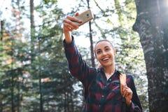 Belle femme de d?placement ?l?gante heureuse prenant la photo au t?l?phone de cam?ra avec le fond de for?t image stock