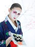 Belle femme de geisha du Japon avec le positionnement de sushi Image stock