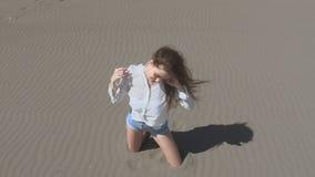 Belle femme de jeune adolescent avec les cheveux de soufflement posant à l'appareil-photo, brune sur la plage appréciant la vie,  banque de vidéos