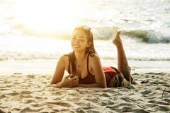 Belle femme de l'Asie se trouvant sur la plage photographie stock