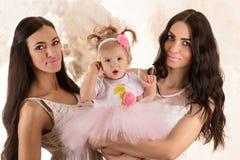 Belle femme de la brune deux avec le petit bébé en nuages Photographie stock libre de droits
