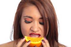 Belle femme de Latina mangeant une orange photographie stock libre de droits