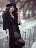 Belle femme de luxe en chapeau noir, manteau trandy et laque de mode Images stock