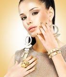 Belle femme de mode avec le maquillage noir et la manucure d'or Photographie stock