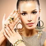 Belle femme de mode avec le maquillage noir et la manucure d'or Photographie stock libre de droits